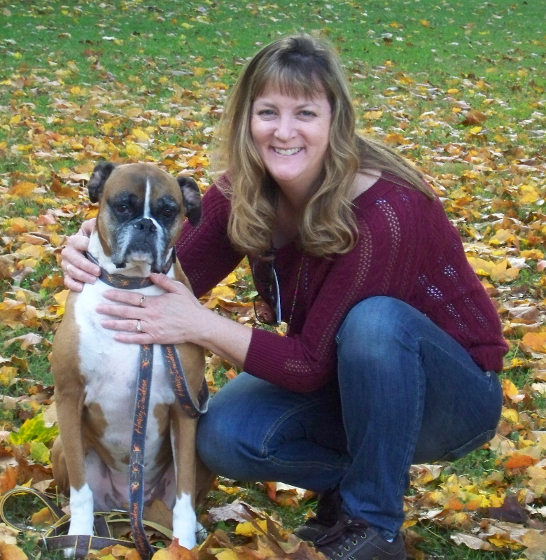 cathy outside in the fall leaves next to a tan and white boxer dog