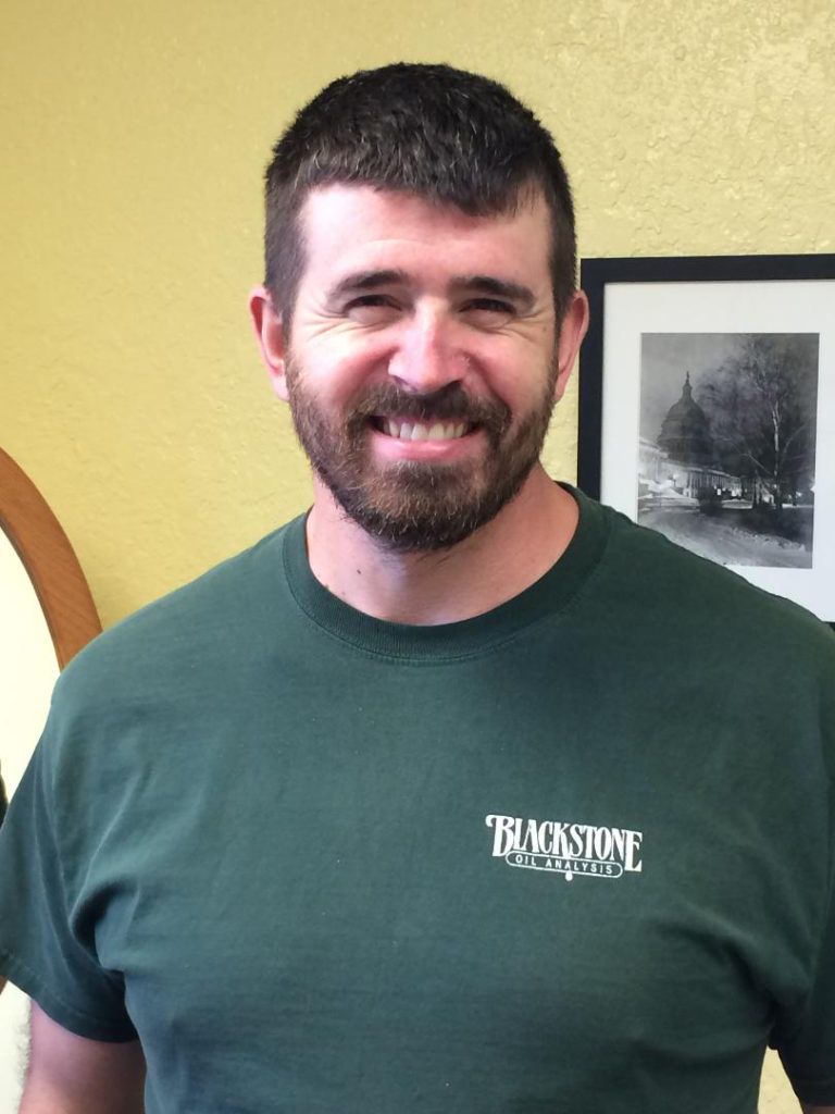 bearded erik wearing a green blackstone shirt, smiling at the camera