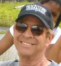 jim stark smiling and wearing a blackstone ballcap and dark sunglasses outside