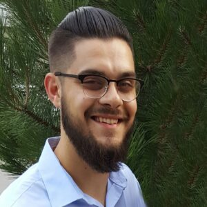 bearded joe with hipster glasses smiling at the camera in front of a pine tree