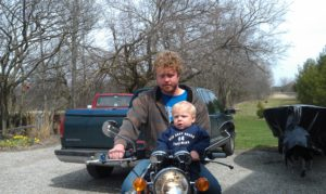 luke outside on a motorcycle with a baby on the seat in front of him