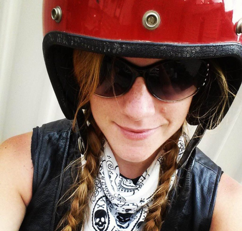 close-up of maggie wearing dark sunglasses, a leather vest, white bandana, and a red motorcycle helmet