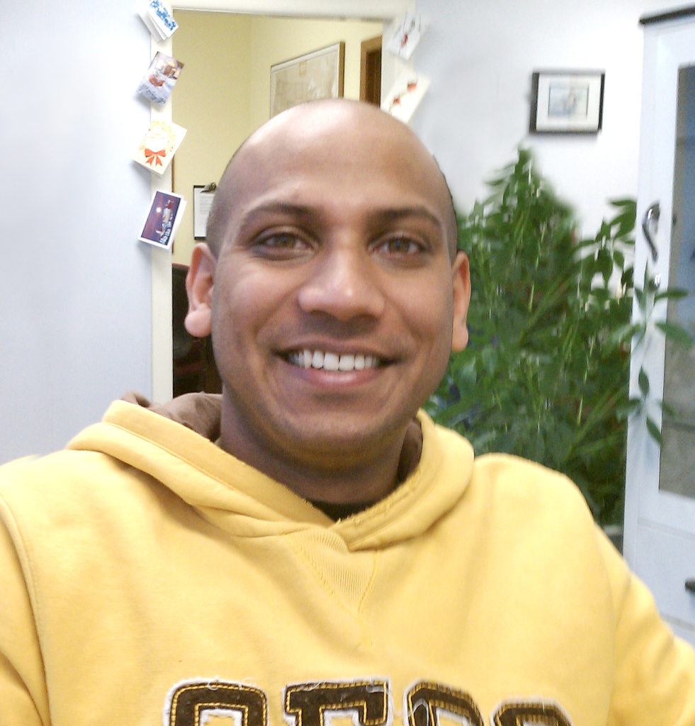 samir wearing a yellow sweatshirt and smiling at the camera