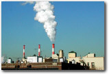 three red-and-white striped smokestacks at a factory putting white smoke into the blue sky