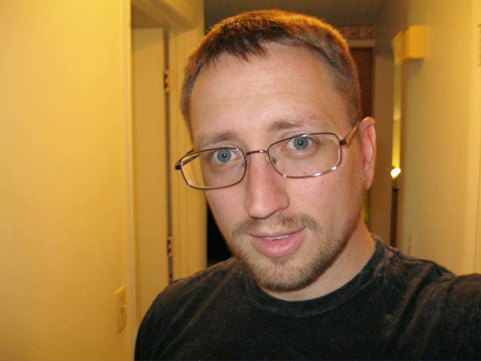 selfie of goateed-travis wearing wire-rimmed glasses in a hallway