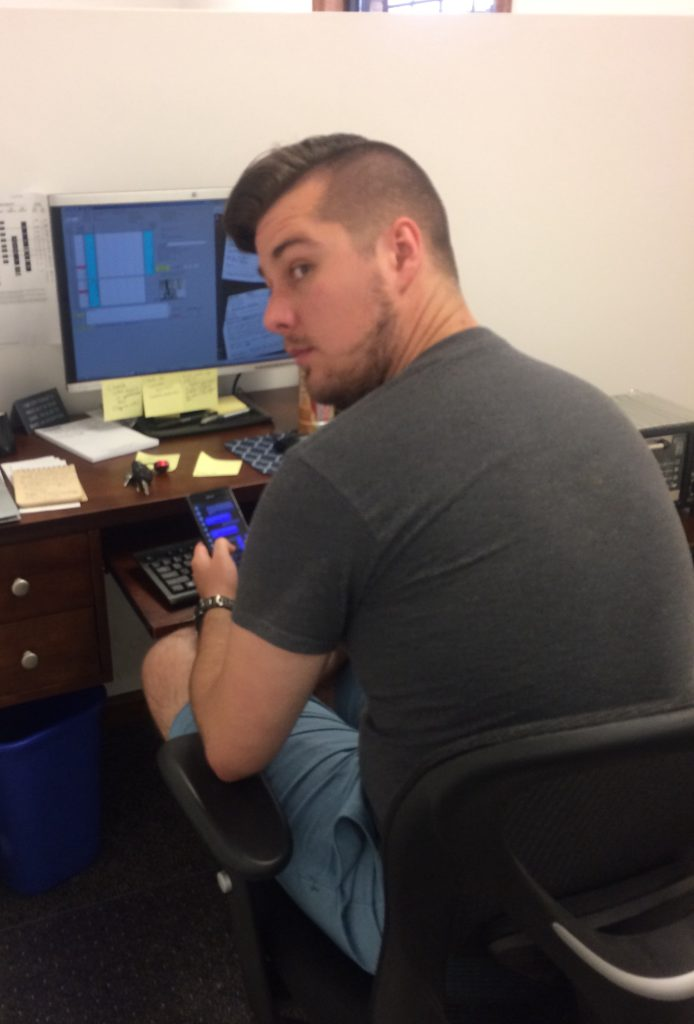 brandon looking sketchy over his shoulder and texting on his phone at his desk in front of a computer