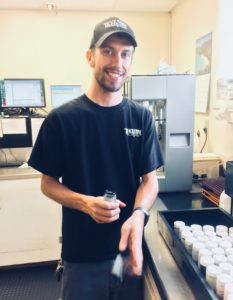 bearded justin wearing a blackstone cap and blackstone shirt, standing in the lab holding an open sample bottle of black oil