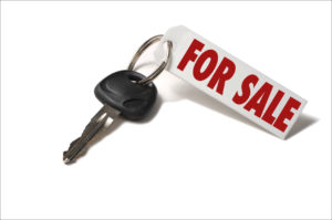 black car key on a ring with a red For Sale tag attached