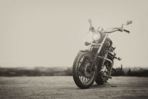 Black and white image of a motorcycle parked with kickstand on a foggy day