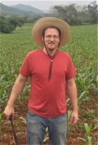 brian wearing a red shirt and straw hat, holding a machete, standing in a corn field