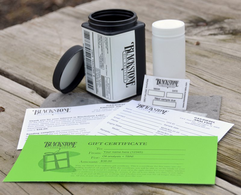 Oil sampling kit disassembled, showing the forms, whlite mailer, oil change sticker, and a green gift certificate