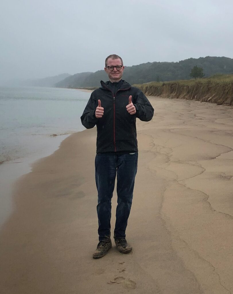 Ben standing on a beach on an overcast day